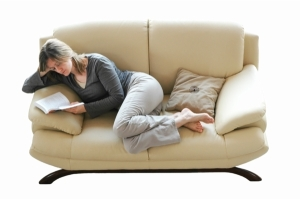 woman resting on sofa reading book