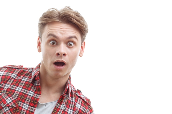 Wow. Surprised young guy expressing amazement with his mouth open standing isolated on white background.